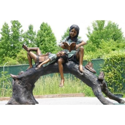 Umelecké Sochy Chlapec a dievča čítajú na drevenej lavičke